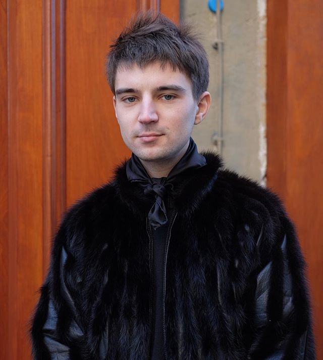 black silk scarf, black shirt and black fur jacket. definitely fashion weeking. not sure if it's a men's or women's fur but he owned it.